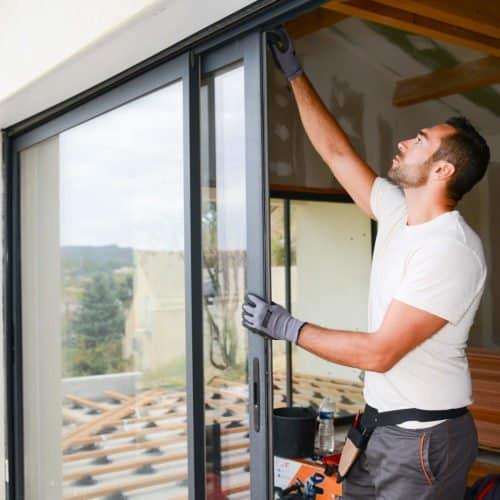 Mann bei Fenstermontage