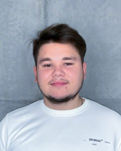 Portrait eines jungen Mannes in weißem Oberteil und mit dunklen Haaren
